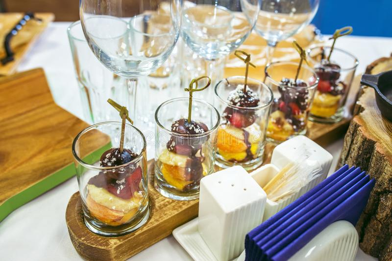 Candy bar with Sweet Pieces of strawberry, grapes, coconut shaving and chocolate designed as a canape. stock photos