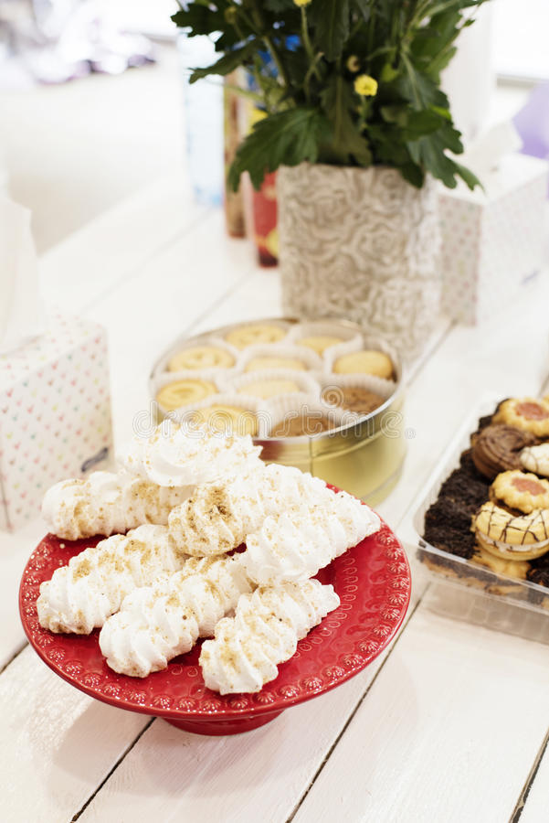 Candy bar Table with sweets, candies, dessert. French meringue cookies in red high plateau, tray. Egg white sweets, biscuits and f. Lowers on a white wooden royalty free stock photo
