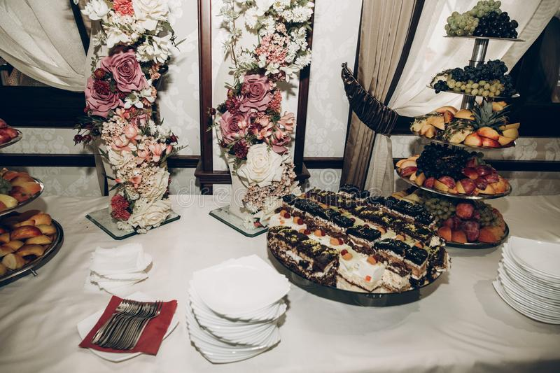 candy bar table at wedding reception with stylish flowers decor, fruits and sweets, luxury catering in restaurant royalty free stock photo