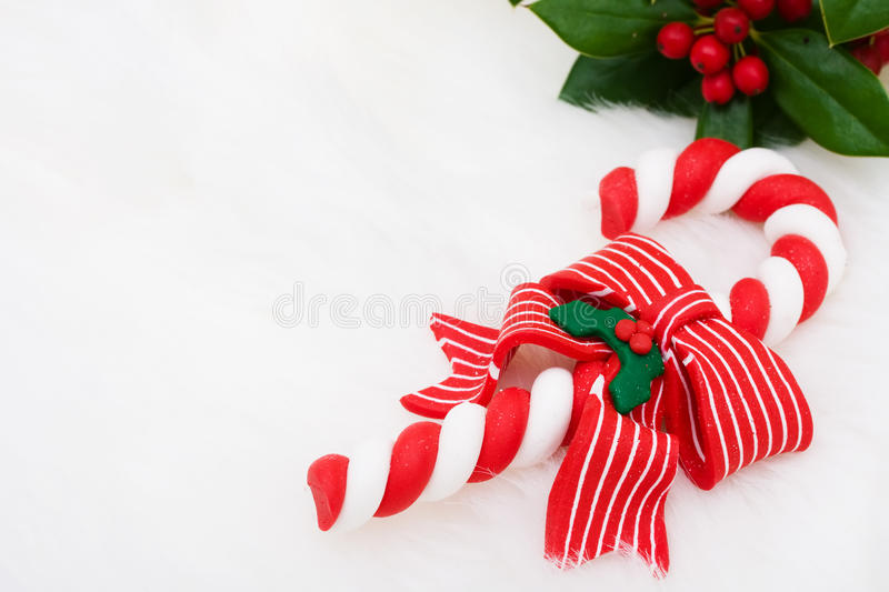 Candy Cane. A candy cane with holly and berries on a white fur background, candy cane royalty free stock photo