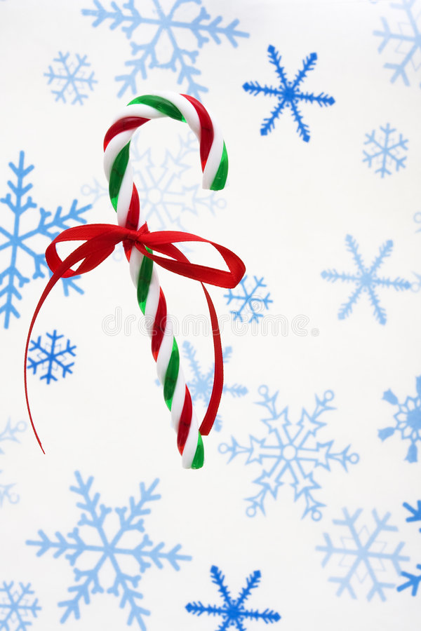 Candy Cane. With red ribbon on snowflake background royalty free stock photography