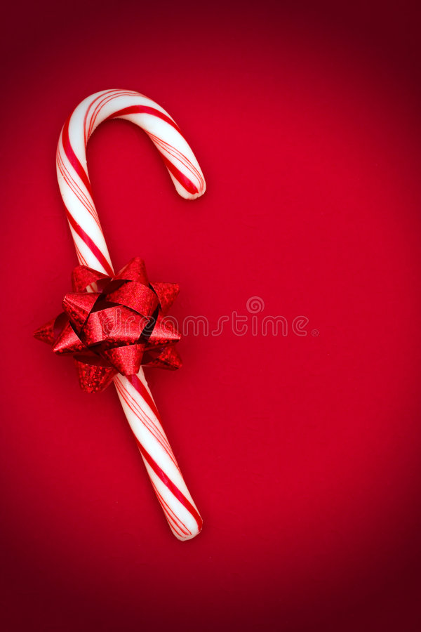 Candy Cane. With red bow on red background stock images