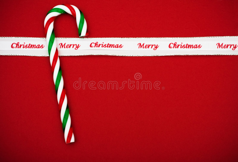 Candy Cane. With merry Christmas ribbon on red background royalty free stock photos