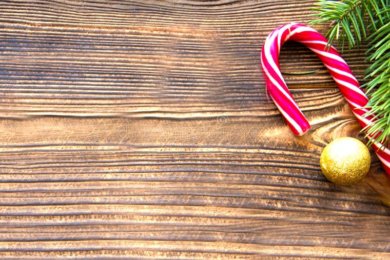 Candy cane on brown background, gold christmas ball decoration and fir tree branches. Copy space for text royalty free stock photo