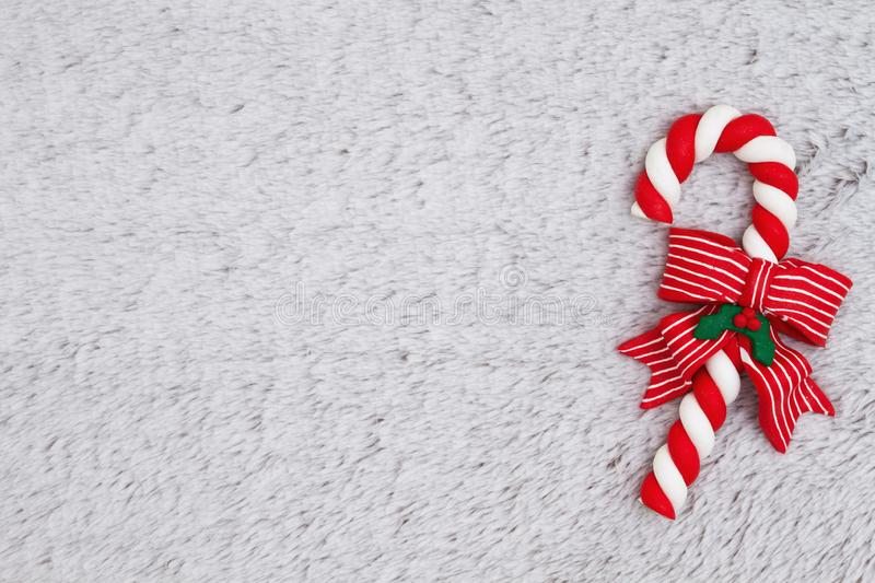 Candy cane on plush gray material background stock image