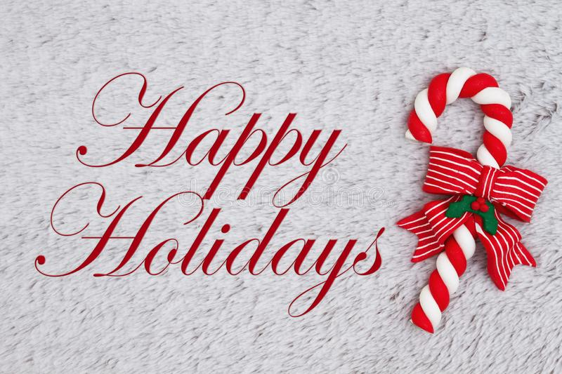 Candy cane on plush gray material with text Happy Holidays. Candy cane on plush gray material with Christmas message of Happy Holidays stock photo