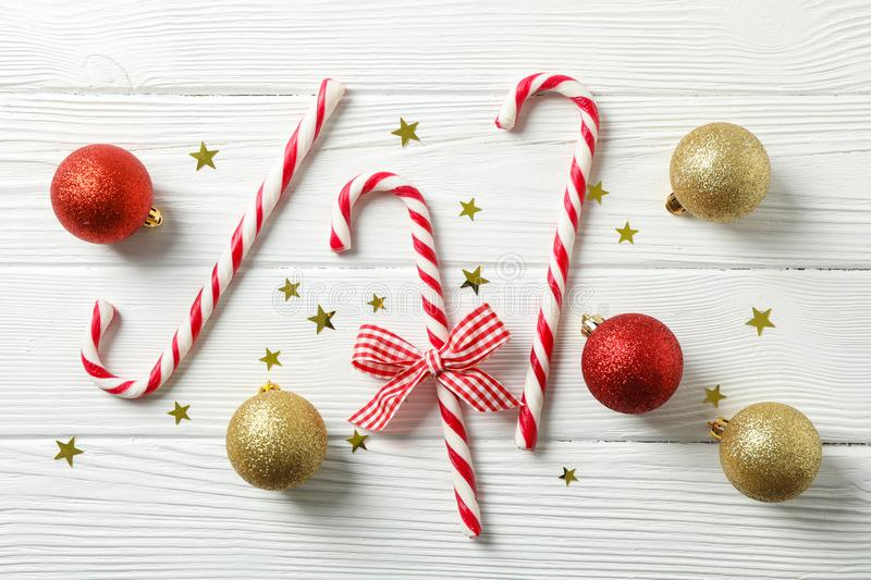 Candy canes and christmas accessories on white wooden background stock photos