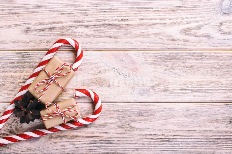 Candy canes and christmas gift on brown wooden rustic vintage background royalty free stock image