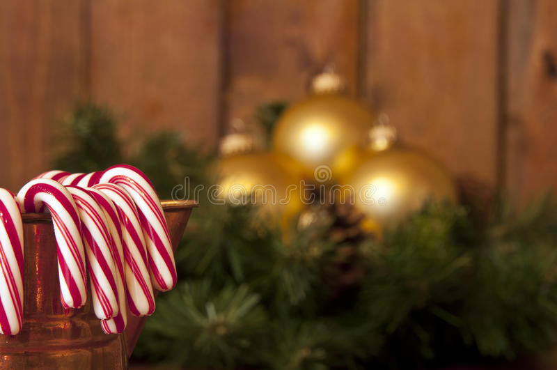 Candy canes. Copper pitcher filled with candy canes with gold Christmas balls and garland in background royalty free stock photos