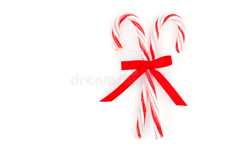 Candy canes tied. Close up of two candy canes tied with ribbon bow on white background stock photography
