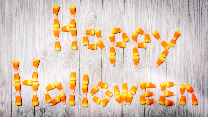 Candy corn spells Happy Halloween. Candy corn spells a decorative Happy Halloween on a wood background royalty free stock images