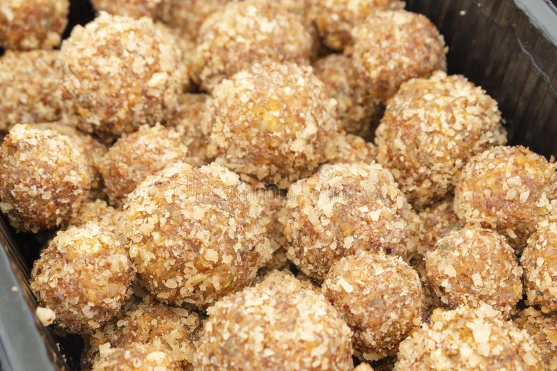 Candy in the form of balls of dried fruit with nuts. Eco sweets. Vegetarianism and raw food diet royalty free stock images