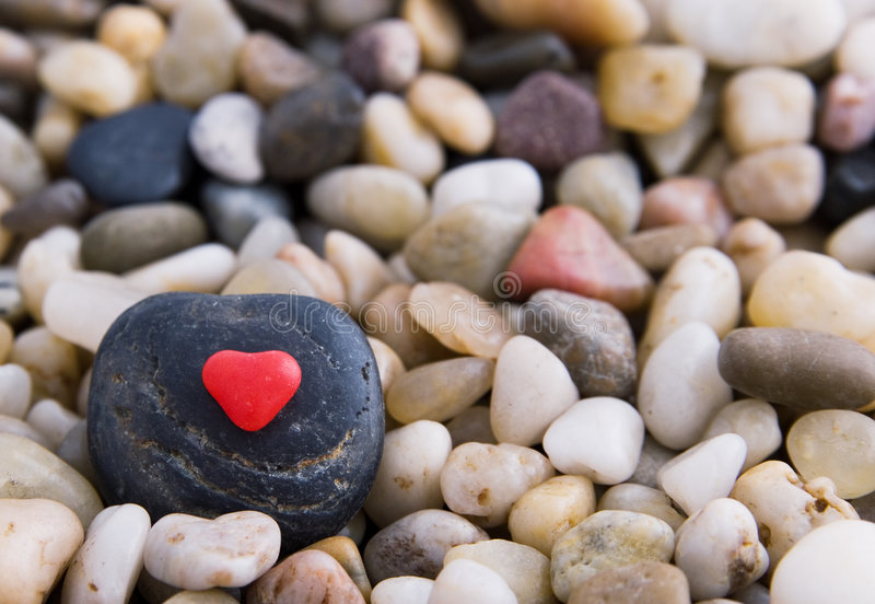 Candy Heart. Red candy heart on a black stone surrounded by gravel royalty free stock photography