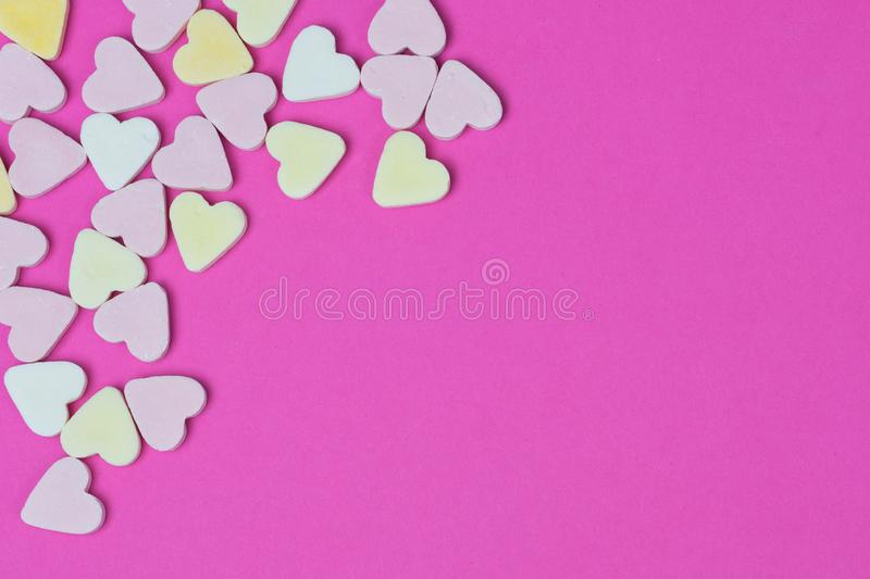 Candy hearts lying in the corner on a pink background stock photos