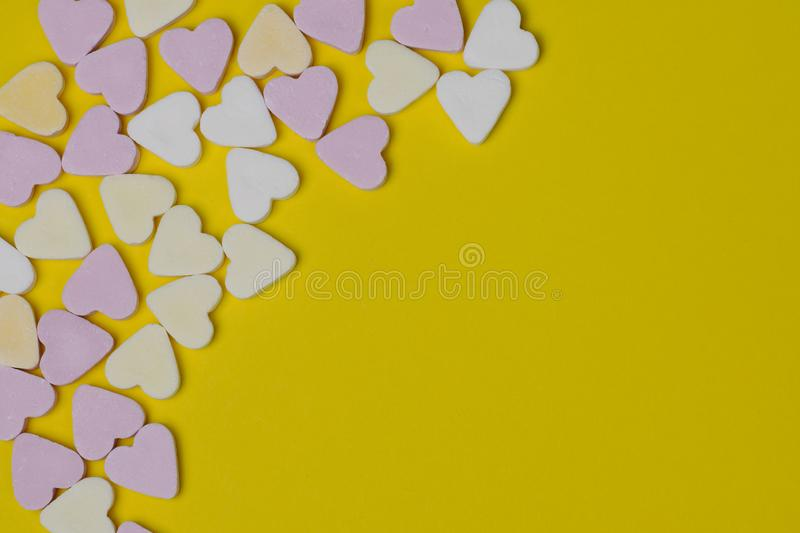Candy hearts lying in the corner on a yellow background stock photography