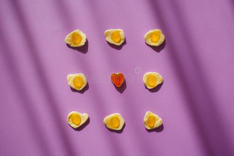 Candy jelly eggs and heart on violet background with shadows. Unique surrealism. Sweets. Marmelade.  royalty free stock images