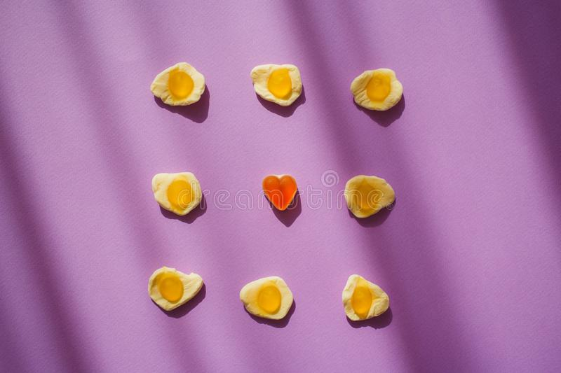 Candy jelly eggs and heart on violet background with shadows. Unique surrealism. Sweets. Marmelade.  stock photos