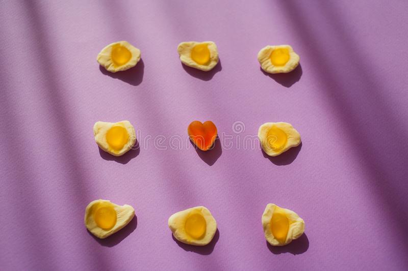 Candy jelly eggs and heart on violet background with shadows. Unique surrealism. Sweets. Marmelade stock photos