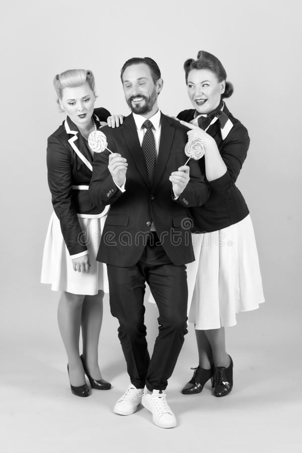 Candy man with two women and lollipops on gray background in stuido stock photos