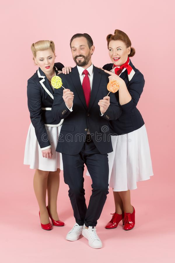 Candyman with two girls and lollipops on rose background. Man propose candies for couple ladies in pin-up style. royalty free stock photography