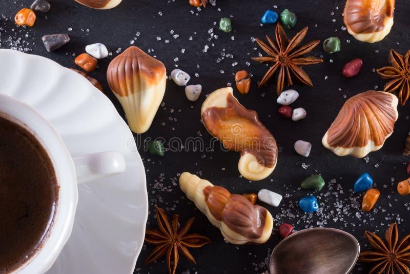 Candy nella forma di frutti di mare con le pietre, lo zucchero e il anice del cioccolato Tazza di coffe caldo Argomento marino su fotografie stock