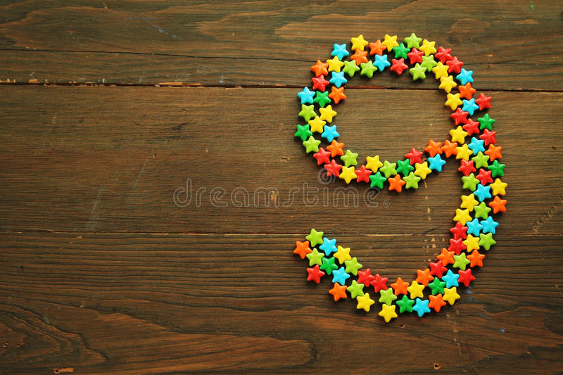 Candy number nine. Number nine made with star shape candies on a wooden table royalty free stock image