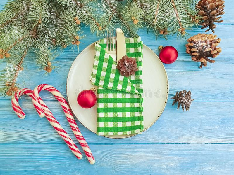 Candy, plate Christmas tree branches holiday festive x on a blue wooden background, fork, knife, banquet, menu royalty free stock photo