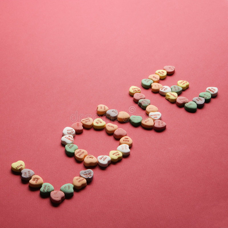 Candy spelling out love. Colorful candy hearts with sayings on them arranged to spell the word love royalty free stock photography