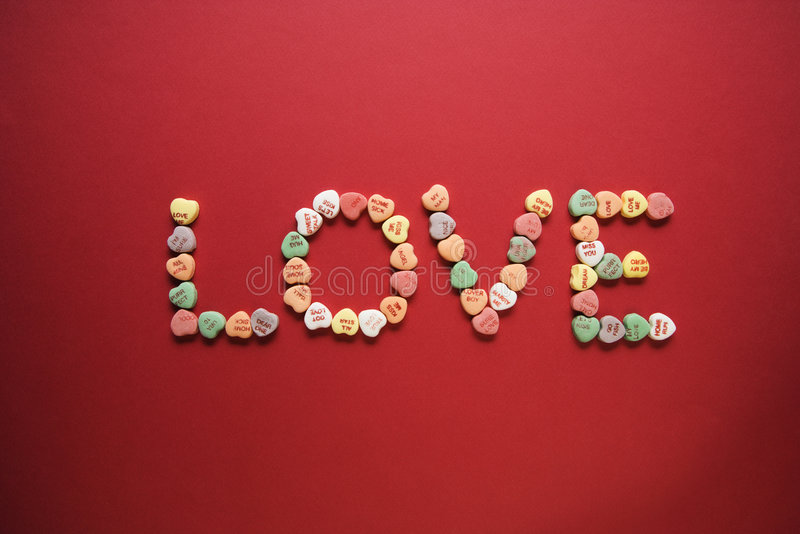 Candy spelling out love. Colorful candy hearts with sayings on them arranged to spell the word love royalty free stock images