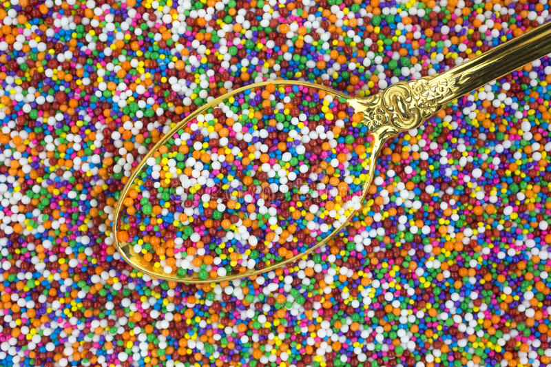 Candy sprinkles with gold spoon stock image