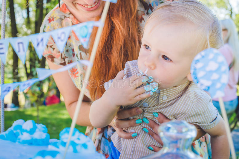 Candy-table. Baby boy eat birthday cake with hands. His mother take him. Birthday party in park on picnic. royalty free stock image
