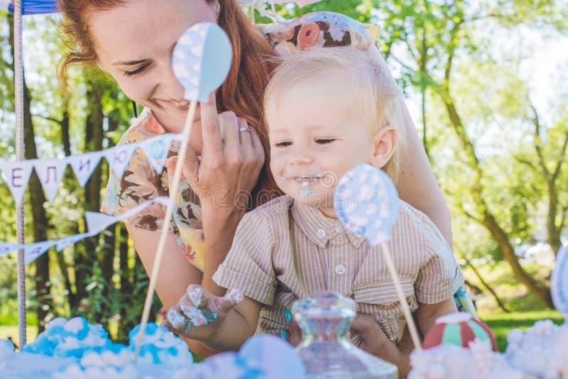 Candy-tavola Il neonato mangia la torta di compleanno con le mani Sua madre lo prende Festa di compleanno in parco sul picnic fotografia stock libera da diritti
