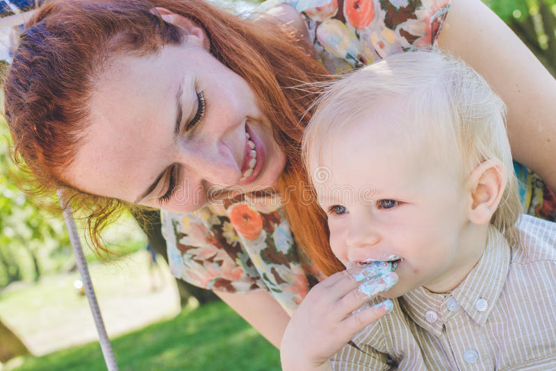 Candy-tavola Il neonato mangia la torta di compleanno con le mani Sua madre lo prende Festa di compleanno in parco sul picnic immagine stock libera da diritti