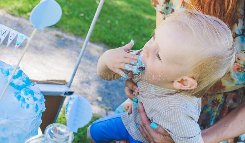 Candy-tavola Il neonato mangia la torta di compleanno con le mani Sua madre lo prende Festa di compleanno in parco sul picnic immagine stock