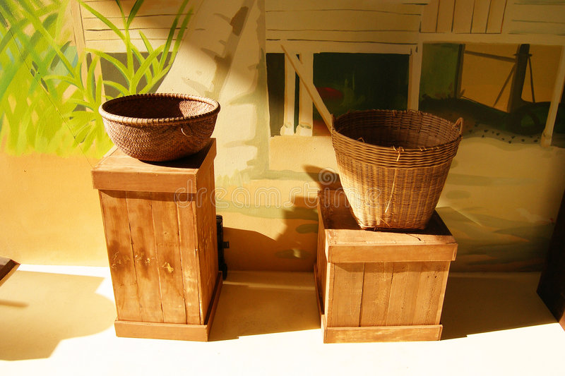 Cane baskets in sunlight. Still life of two rustic rattan baskets in different styles, placed on wooden crates. Handicraft items of the tropical southeast asian stock image