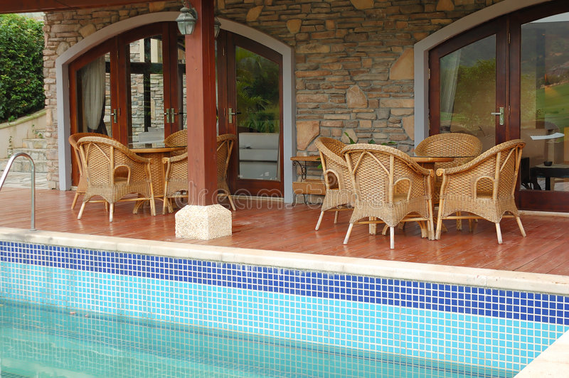 Cane chairs. And table near swimming pool royalty free stock photos