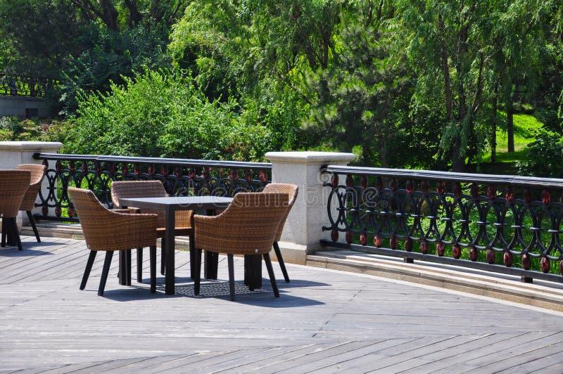 Cane Chairs e tavola sul pavimento di legno fotografia stock
