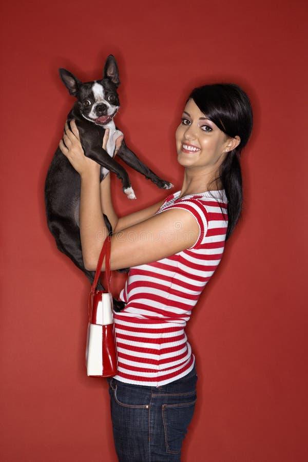 Cane del Terrier di Boston della holding della giovane donna. fotografia stock libera da diritti