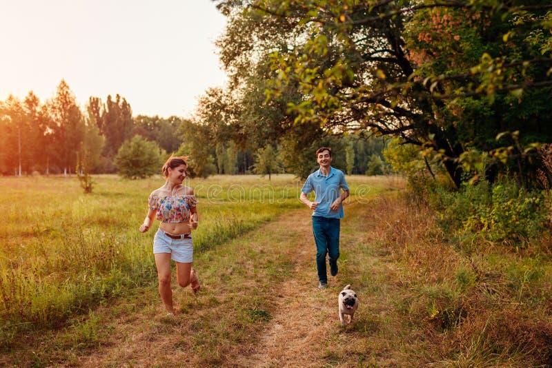 Cane di camminata del carlino delle giovani coppie nel funzionamento felice del cucciolo della foresta di autunno avanti e divert immagini stock libere da diritti