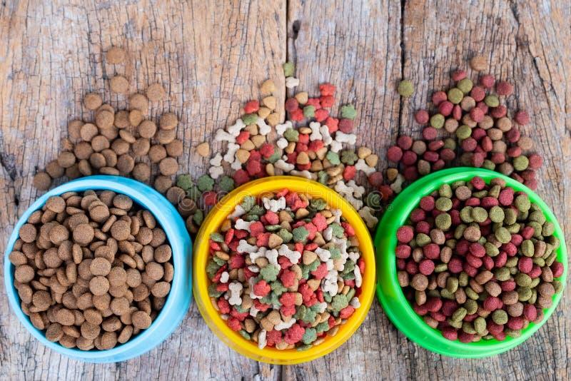 Cane e cibo per gatti a secco in ciotola contro su fondo di legno immagine stock