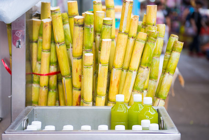 Cane and fresh sugarcane juice in bottle. For sale in market stock image