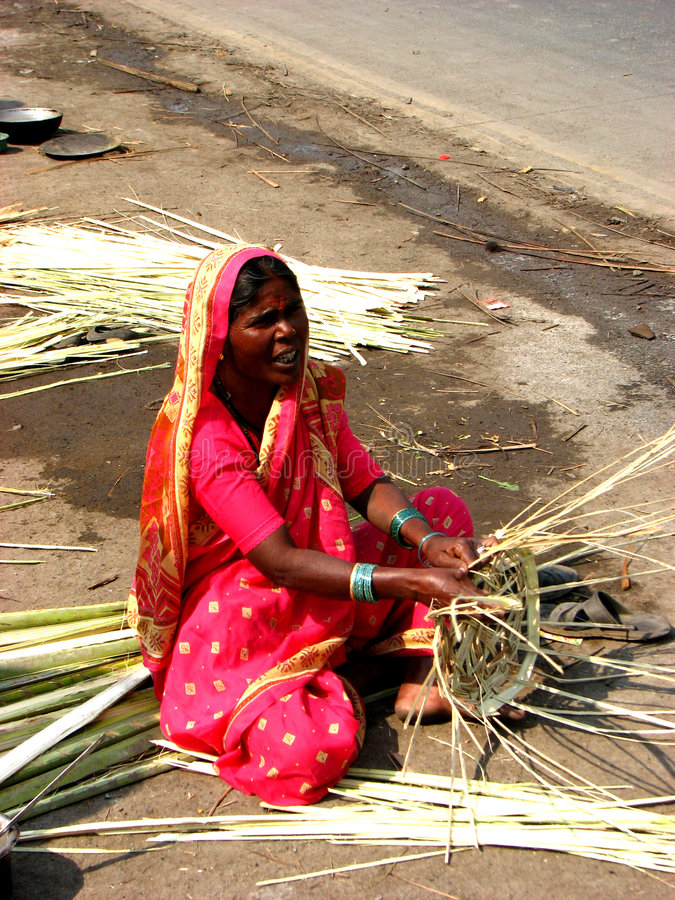 Cane Jobs. An Indian woman living on the streets making cane baskets for a living stock image