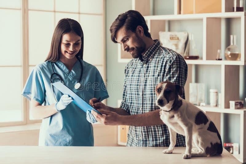 Cane sveglio con il proprietario in veterinario Clinic fotografia stock libera da diritti
