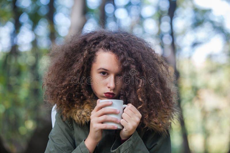Caneca adolescente da terra arrendada da menina do cabelo encaracolado no parque fotografia de stock
