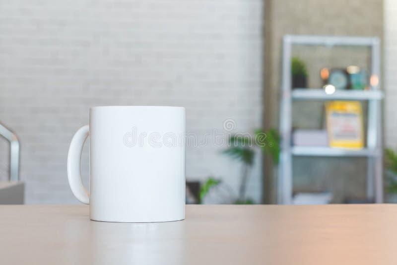 Caneca branca na tabela e no fundo moderno da sala Copo vazio da bebida para seu projeto Pode p?r o texto, a imagem, e o logotipo fotos de stock royalty free