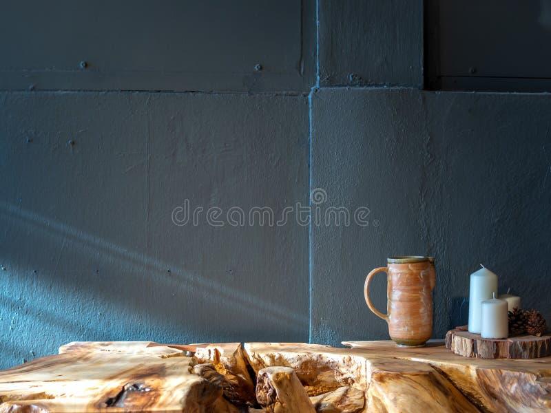 Caneca cerâmica com a decoração branca das velas da cera na tabela de madeira no fundo pintado azul do muro de cimento fotografia de stock