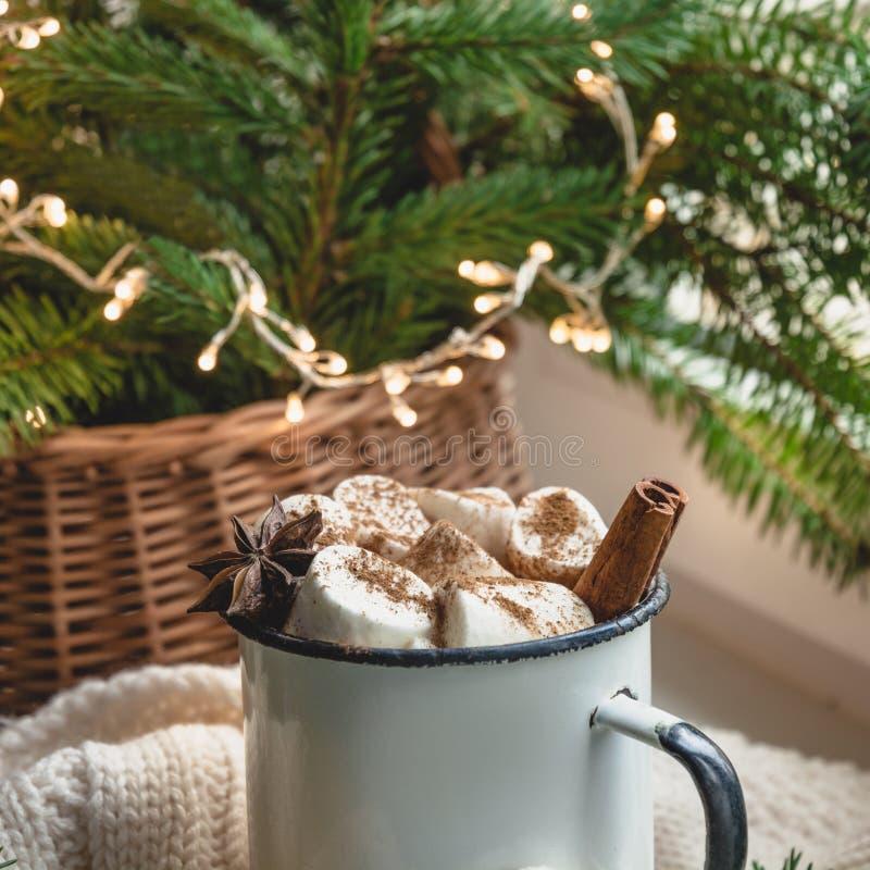 Caneca de aquecimento do inverno de chocolate com o marshmallow na soleira com a decoração da árvore de Natal fotografia de stock royalty free