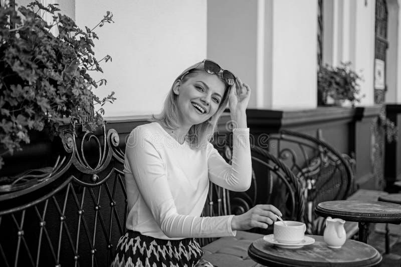 A caneca de bom café na manhã dá-me a carga de energia A cara feliz elegante da mulher tem o terraço do café do café fora Menina foto de stock