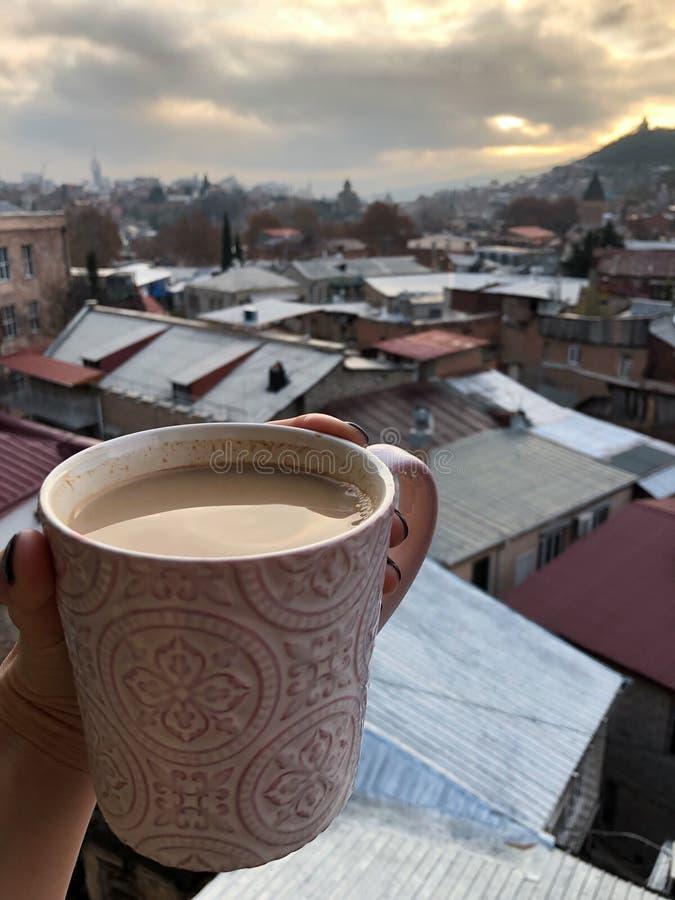 Caneca de café à disposição e uma vista bonita de Tbilisi imagem de stock