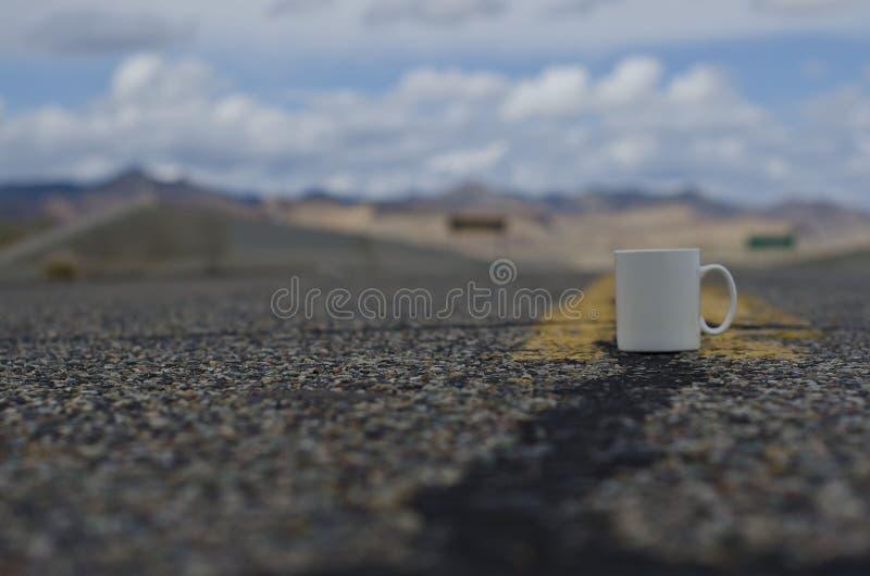 Caneca de café branco vazia de solo em uma estrada vazia da paisagem fotos de stock royalty free